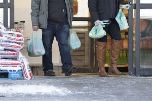 Shoppers leave Independent Grocer with plastic bags of groceries in Whitehorse on Feb. 5. Zero Waste Yukon is launching a petition that will call on the Yukon government to impose a fee for single-use bags across the territory.